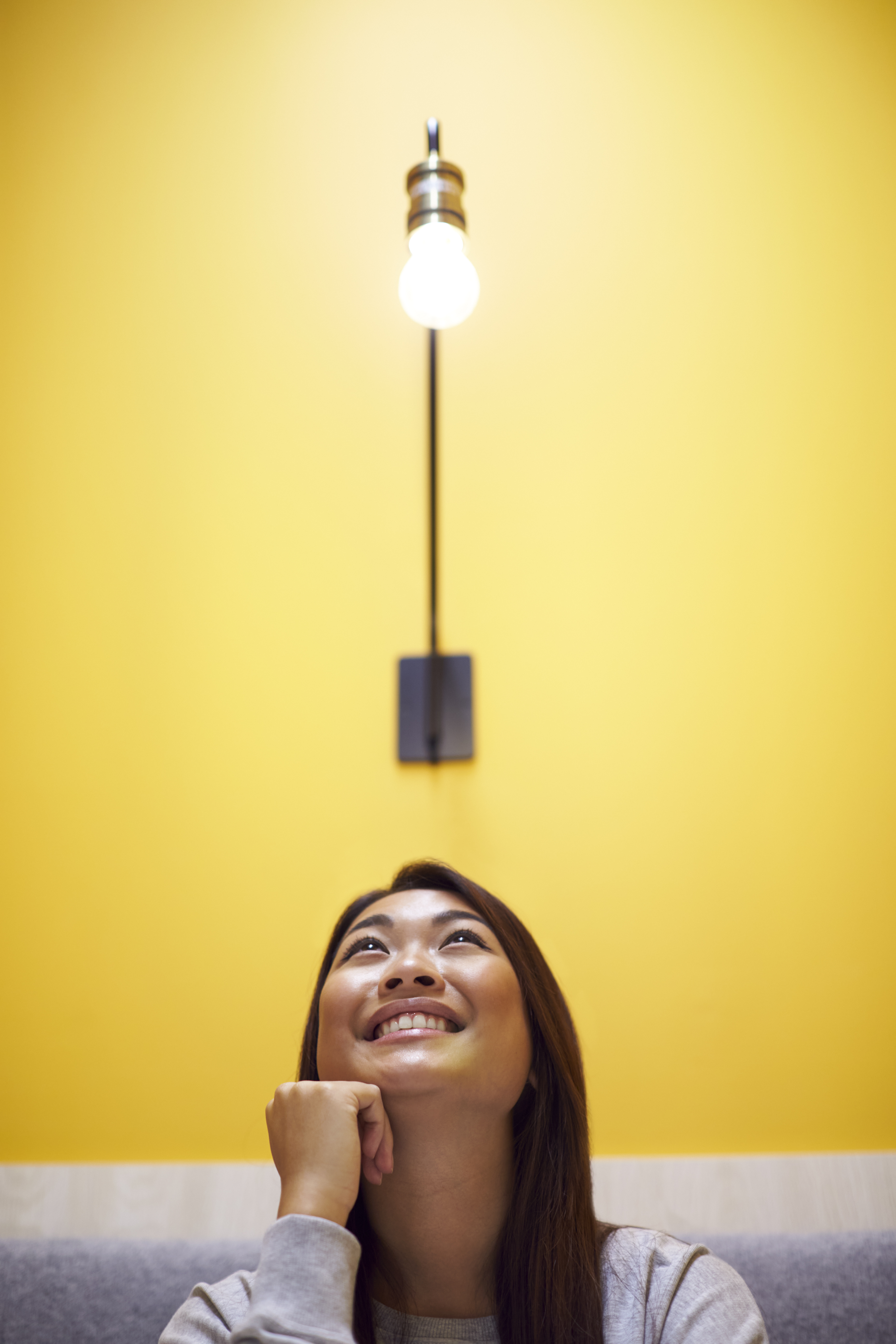 woman-sitting-under-light-bulb-in-office-suggestin-BMD9E2S
